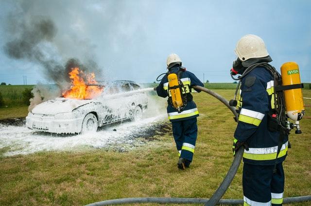 Strażacy gaszący płonący samochód